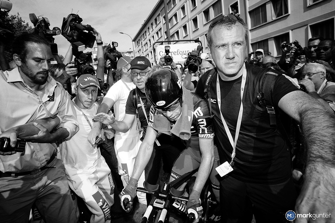 Cadel Evans had just finished the Time Trial in Grenoble and with only one stage to go in the 2011 Tour de France he was virtually assured the overall win. A few strong men were there to help guide him through the media scramble.