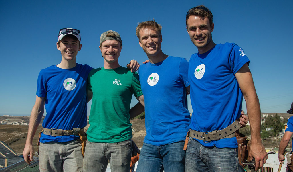 Chad Haga, Ben King, Guy East and Jesse Anthony on the roof of a house during a Hope Sports build.