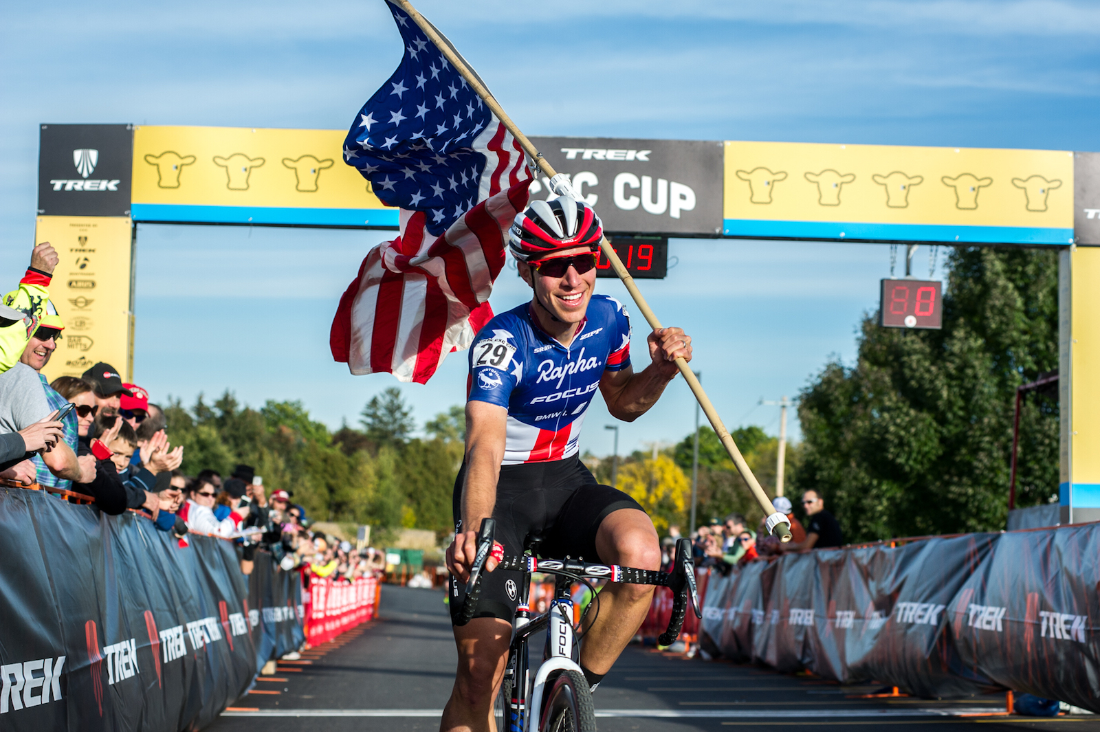 """Ethan Glading, United States. """"Jeremy Powers carries an American flag across the finish line as he wins the 2015 edition of the Trek CXC Cup cyclocross race in Waterloo, Wisconsin."""" Professional. @thepenultimatestage"""