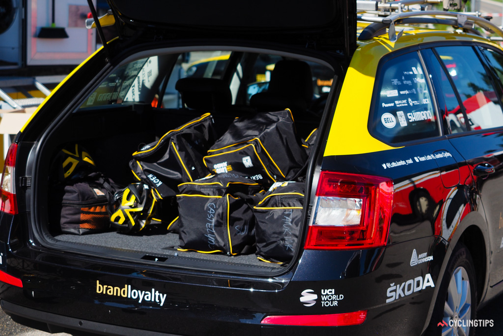 Rain bags are piled into the back of a team car in preparation for a training ride.