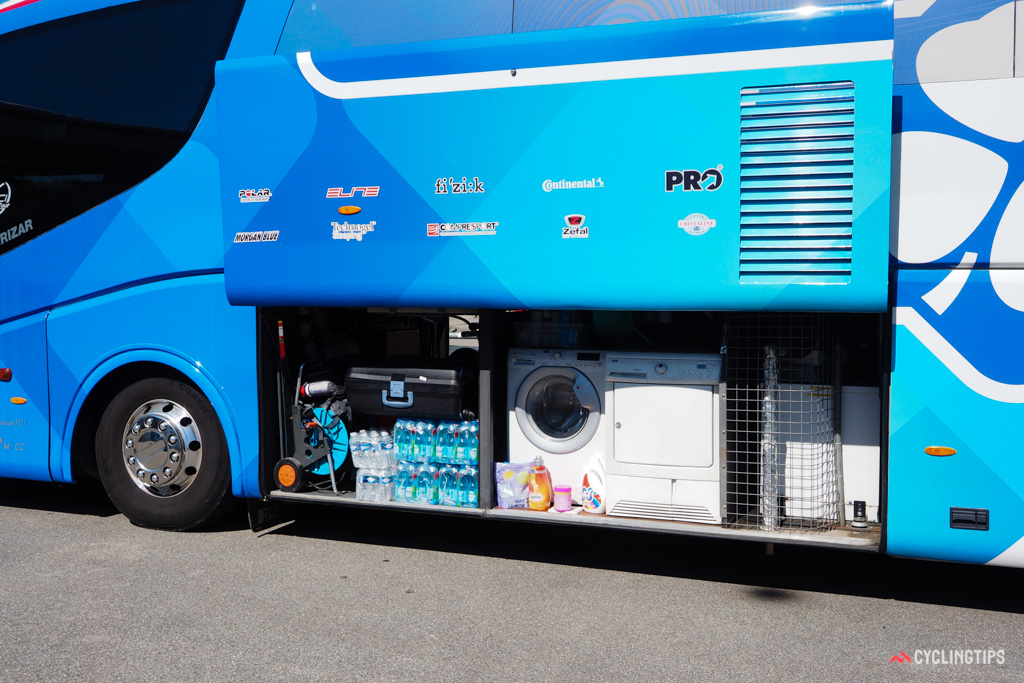 The undercarriage of team buses are packed with supplies and equipment.