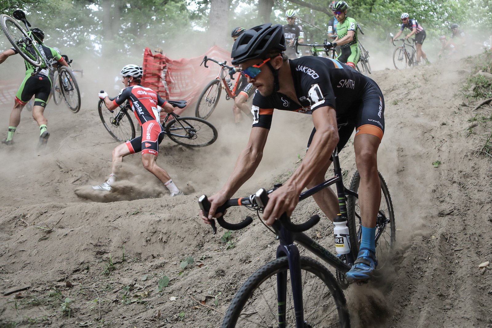 """Meg McMahon, United States. """"The first US C1 Cyclocross race of the season in Rochester NY. It was an extremely hot and therefore a dusty dry course. Danny Summerhill decided to ride a different line. As a sports photographer you prepare and as I watched the pre ride there were several riders exploring different lines in this technical section. I had a feeling on the first lap some chaos would ensue."""" Professional. @mcmahon_meg"""