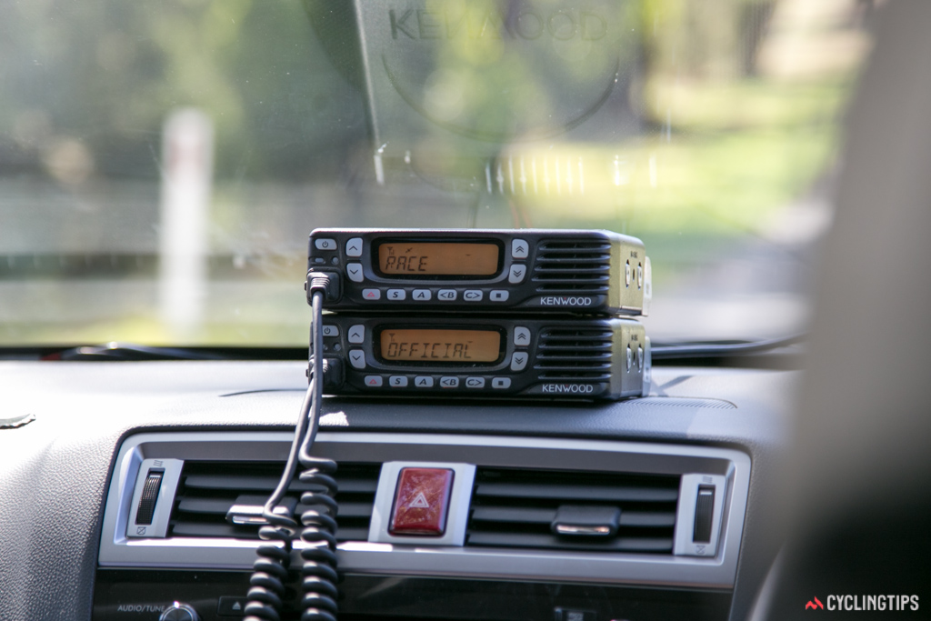 Two radios in the commissaire's car, the top one set to the Race channel, the bottom one set to Official.