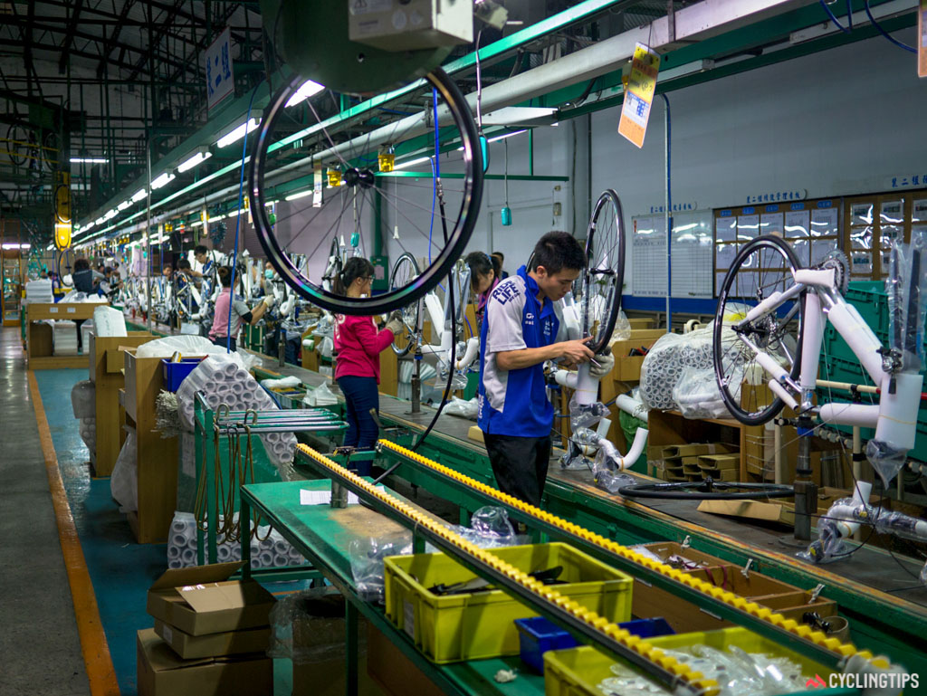A wheel is dropped from a conveyor belt overhead into the assembly line.