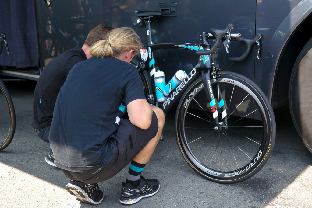Team mechanics check over the Di2 shifting set up using an iPhone before the start of stage seven n L'Isle-Jourdain.