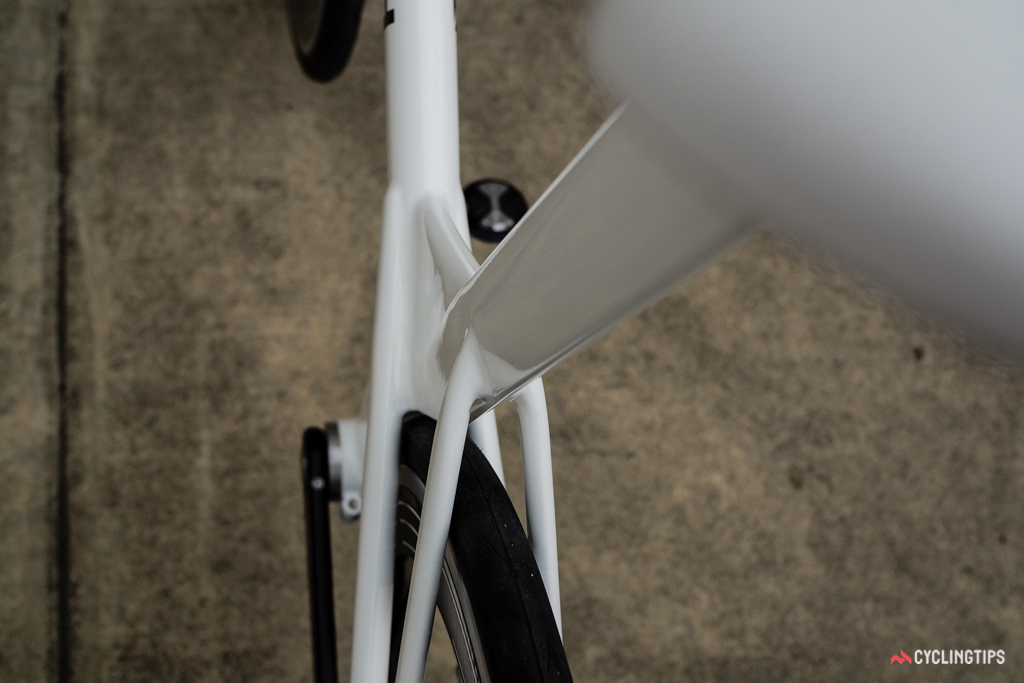 The rear wheel tucks closely behind the sculpted seat tube.