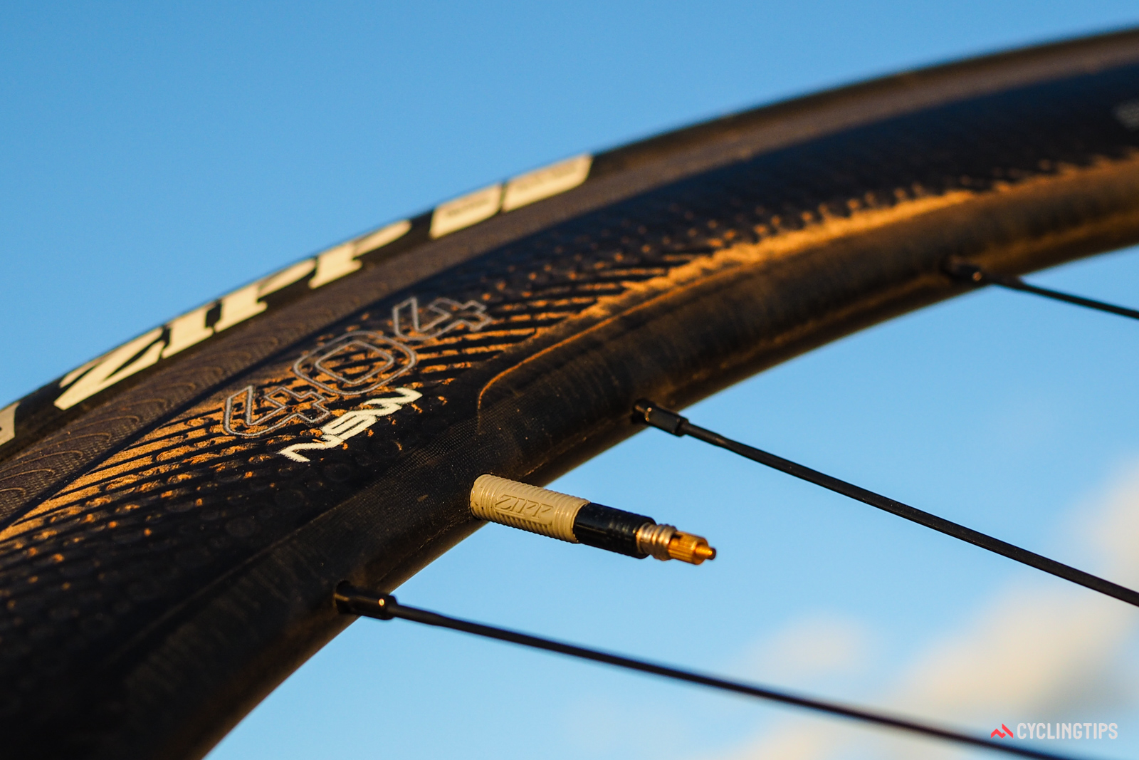 Each set of Zipp 404 NSW wheels comes with special brake pads, titanium skewers, and valve extenders made for Zipp by Silca. The silicone rubber coating seems like a minor detail, but it keeps the valve from rattling without the need for any supplemental tape.