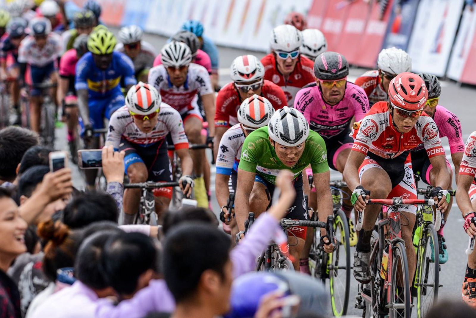 """Chen Xu Jie, China. """"Topic: Dirt Circle. The last stage of Tour of Fuzhou, it rained before the race which made the road was wet and dirty. After several circles, all the dirt stick on the cyclists' faces."""" Professional. @neichanging"""