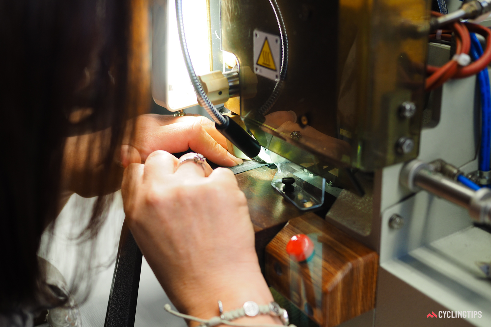Glue is applied to bonded saddle cover sections with a machine, but the material is guided by hand.