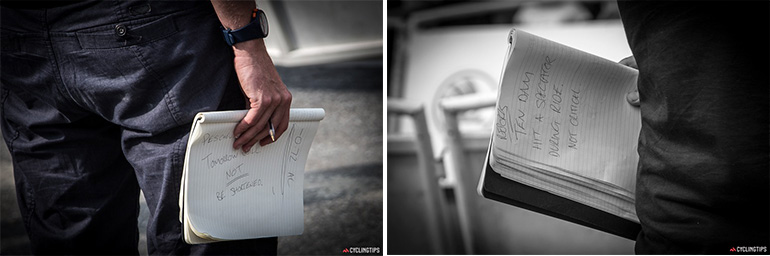 """While Tommo and his guest presenter do a live wrap-up of the day's stage, Stu writes notes shows them to the presenters, if needed, while they're talking. The note on the left says """"Tomorrow will not be shortened"""", a clarification about the possibility of the Alpe d'Huez stage being weather-affected. The note on the right says """"Ten Dam hit a spectator during ride. Not critical."""" This was from the stage 17 time trial."""